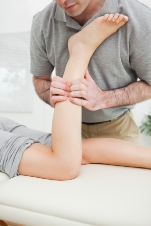 Close-up of a man massaging the leg of a woman in a room photo