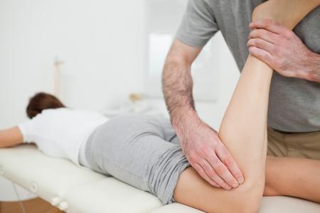 fisioterapia: Mujer tendida al ser masajeado por un hombre en una habitaci�n