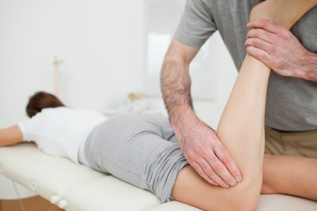 neuromuscular reeducation: Woman lying while being massaged by a man in a room