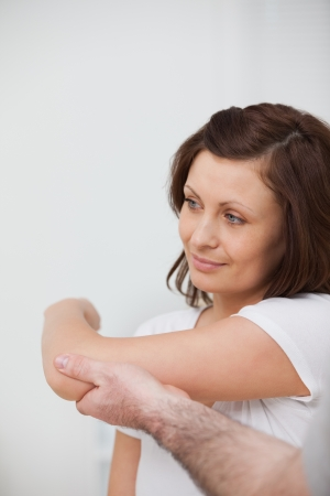 Smiling woman being stretched by a man in against grey background Stock Photo - 16206620