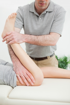 Close-up of a men stretching the leg of a woman in a room photo