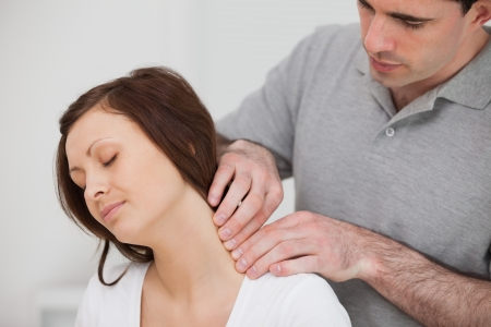 herniated: Man massaging the neck of his patient in a medical room Stock Photo