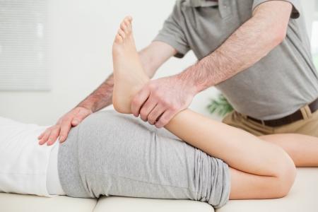tendones: Primer plano de una mujer tendida mientras se estira en una habitaci�n Foto de archivo