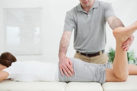tendones: Mujer tendida mientras se estira por un m�dico en una sala de