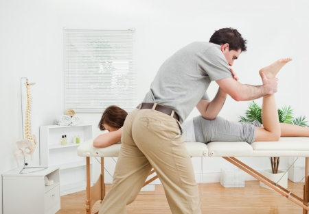 Brunette woman being stretched by a physiotherapist in a room Stock Photo - 16202797