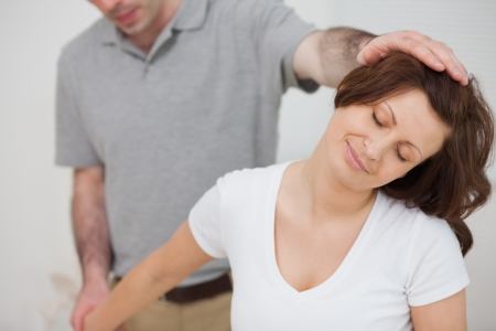 neuromuscular reeducation: Smiling woman being stretched by a physiotherapist in a room