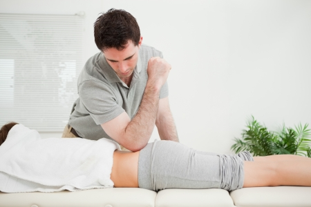 spinal conditions: Man pressing the back of a woman with his elbow in a room Stock Photo