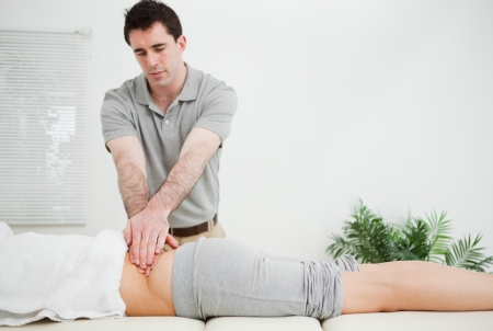 Masseur standing while massaging the back of his patient in a room photo
