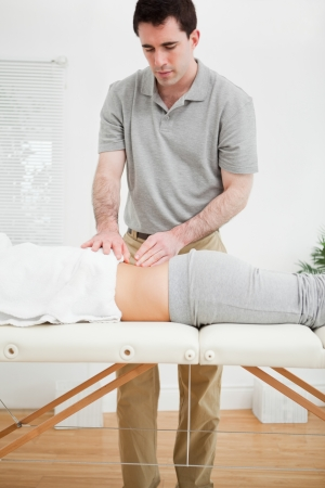 spinal disc herniation: Brunette masseur standing while massaging the back of a woman in a room