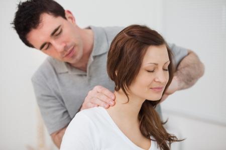 fisioterapia: Mujer sonriente sentado al ser masajeado por un hombre en una habitaci�n Foto de archivo