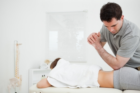 spinal conditions: Brunette physiotherapist massaging a woman with his elbow in a room