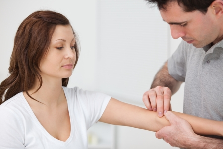 neuromuscular reeducation: Doctor examining the arm of a patient in a room Stock Photo