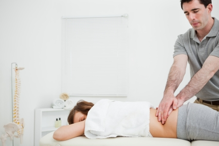 sacroiliac joint: Masseur massaging the back of a brunette woman in a room