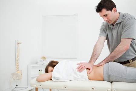 Serious practitioner massaging the lower back of a woman in a room photo