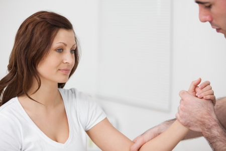 naprapathy: Woman sitting while a man examine her arm in a room