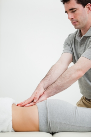 sacroiliac joint: Close-up of a masseur massaging the back of a woman in a room Stock Photo