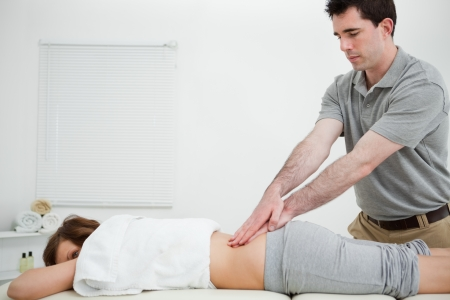 spinal disc herniation: Man standing while massaging the back of a woman in a room