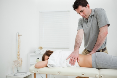 sacroiliac joint: Brown-haired doctor massaging the back of a woman in a room