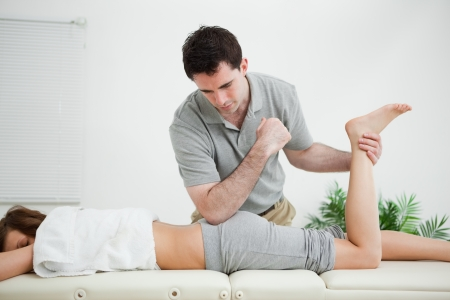 muscle retraining: Woman lying forward while a man stretched her leg in a room