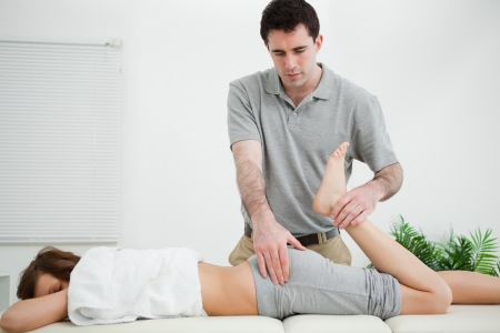 woman buttocks: Woman lying while being stretched by a physiotherapist in a room Stock Photo