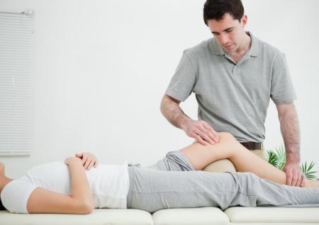 dolor muscular: Mujer acostada sobre su espalda mientras se masajea en una habitación