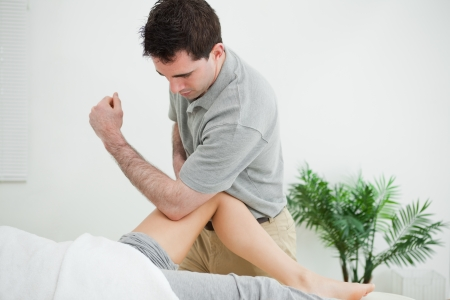 muscle retraining: Brown-haired physiotherapist massaging the leg of a woman in a room
