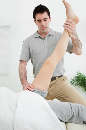 muscle retraining: Physiotherapist raising the leg of a patient in a room Stock Photo