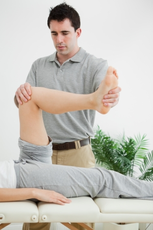 muscle retraining: Brunette physiotherapist manipulating a leg in a room
