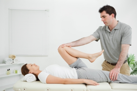 neuromuscular: Woman lying on her back while being stretched in a room