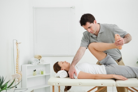 Brunette physiotherapist stretching a leg while standing in a room