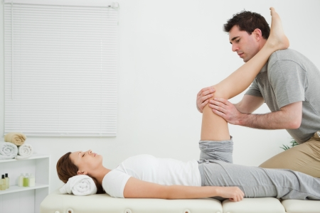 naprapathy: Man massaging a knee while placed it on his shoulder in a room
