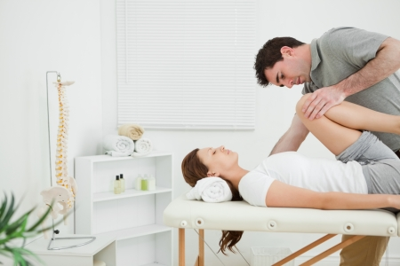 joint mobilization: Brunette woman being stretched while she is lying in a room