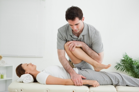 neuromuscular reeducation: Brown-haired woman being stretched by a man in a room