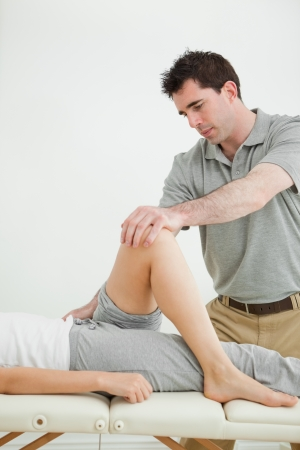 naprapathy: Serious physiotherapist stretching a leg while standing in a room