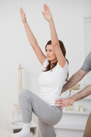 postural integration: Woman doing exercise while a man is putting his hands on her hips in a room