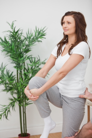 naprapathy: Woman standing while stretching her leg in a room
