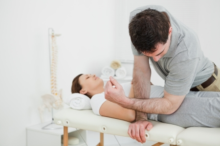 Physiotherapist massaging the pelvis of a woman in a medical room Stock Photo - 16205248