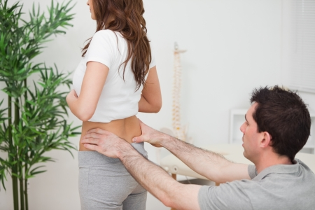 Doctor sitting while examining the hips of a woman in a room Stock Photo - 16207713
