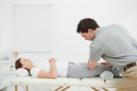 massaged: Woman lying on her back while being massaged by a man in a room