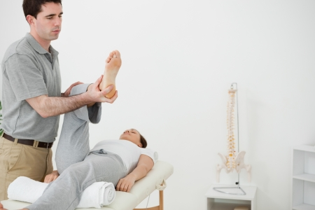 Brunette physiotherapist manipulating the leg of a woman in a room Stock Photo - 16202643