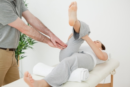 Woman stretching her leg while a man is massaging her in a room photo