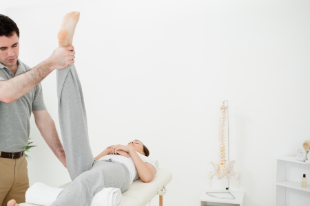 muscle retraining: Physiotherapist raising the leg of a woman in a room