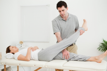 joint mobilization: Brunette physiotherapist raising the leg of a patient in a room