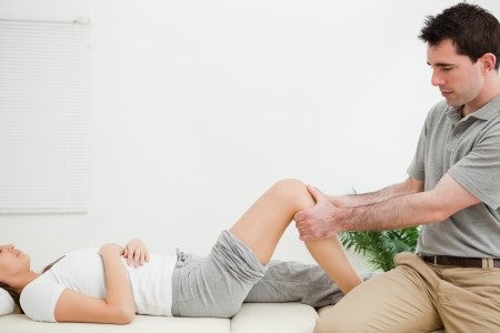 lower limb: Physiotherapist sitting while massaging a knee in a room