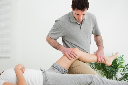 neuromuscular reeducation: Masseur massaging the leg of a woman while placing it on his thigh in a room