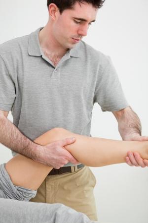 osteopata: Oste�pata serio examen de una pierna de su paciente en una habitaci�n