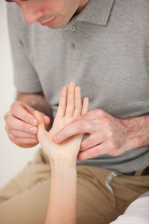 Man massaging the thumb of a woman in a room