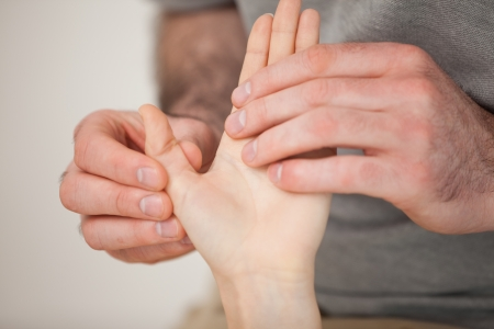 muscle pain: Thumb being massaged by a doctor in a room Stock Photo