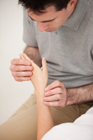 muscle retraining: Serious doctor looking at the wrist of a patient in his office
