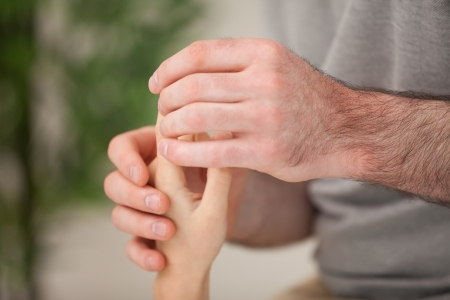 joint mobilization: Hand of a patient being massaged in a room Stock Photo